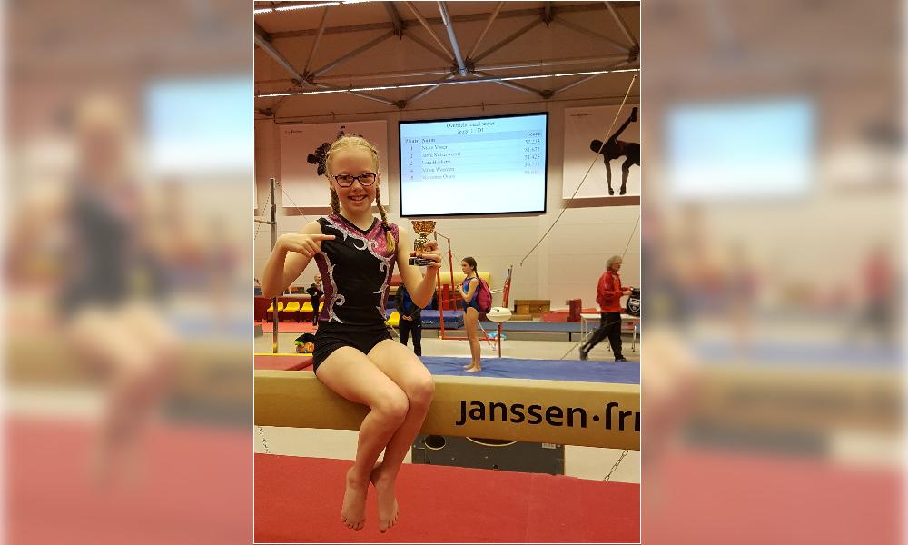 Op de foto Lara Hoekstra met haar gewonnen beker om de balk en op de achtergrond de uitslag.